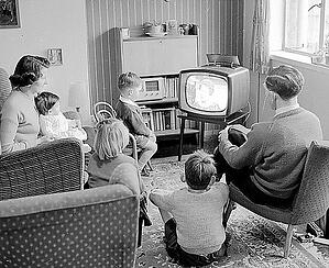 black and white old photo of family around TV